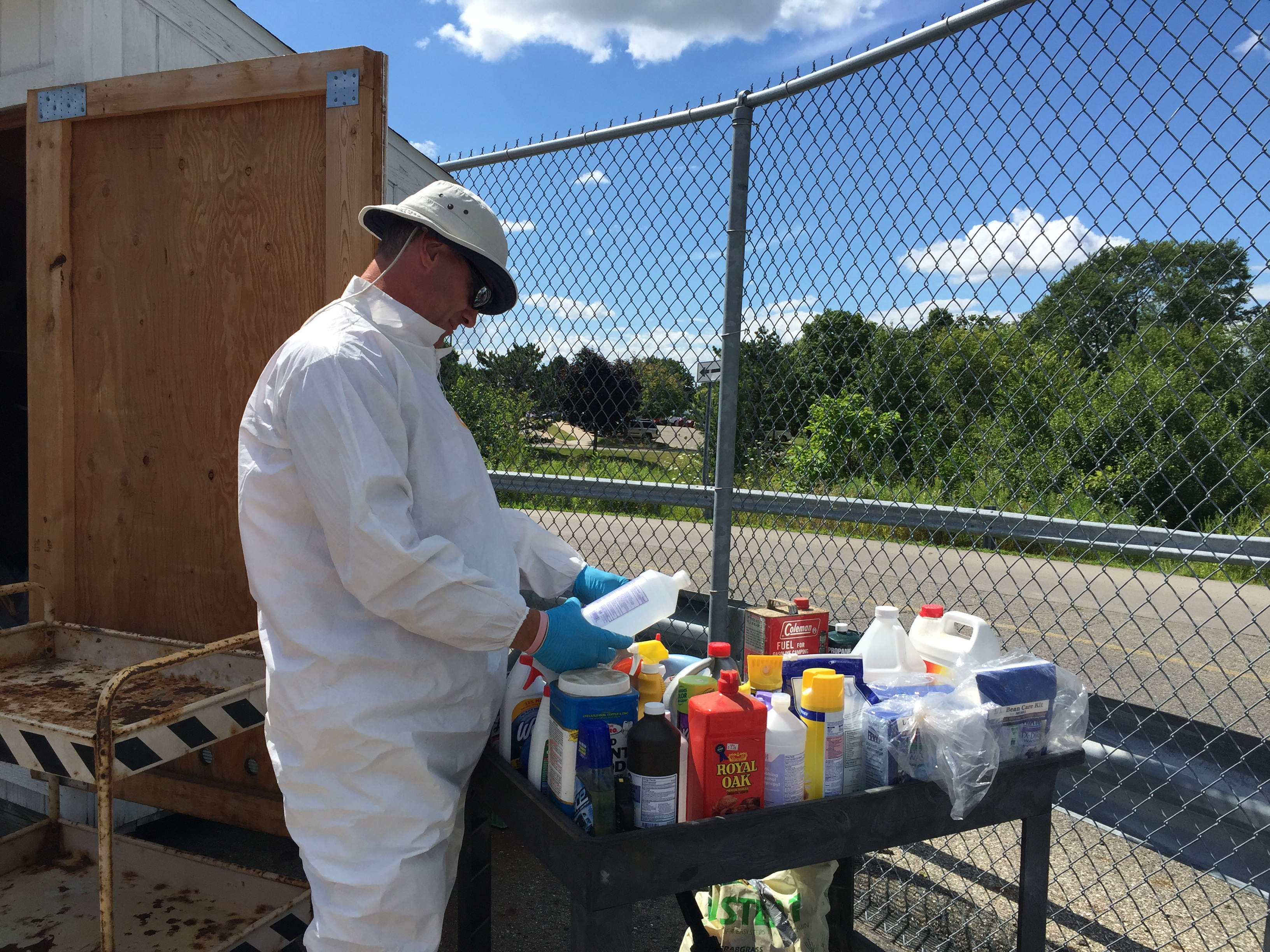 Picture of Environmental Health employee sorting collected household hazardous waste